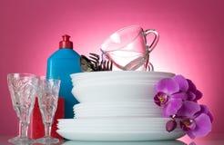 Placas, cubiertos, cristales y botella con el detergente en rosa Fotos de archivo libres de regalías
