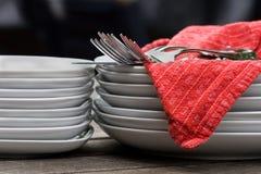Placas, cutelaria, & guardanapo na tabela ao ar livre Foto de Stock