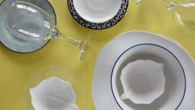 Placas da porcelana e vidros de vinho diferentes no fundo amarelo fresco video estoque