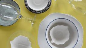Placas da porcelana e vidros de vinho diferentes no fundo amarelo fresco vídeos de arquivo