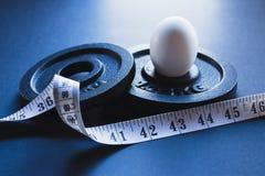 Placas de aço do halterofilismo com fita métrica e o um ovo cozido branco Foto de Stock