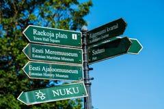 Placas de calle direccionales verdes escritas en estonio con traducciones inglesas fotos de archivo libres de regalías
