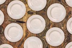 Placas de cena del vintage, cuchillos, bifurcaciones y cucharas en una tabla vieja Imagenes de archivo