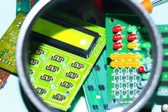 Placas de circuito eletrônico em um fundo azul mais uma lupa fotografia de stock