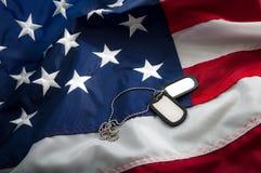 Placas de identificación militares de los E.E.U.U. y la bandera americana Imagen de archivo