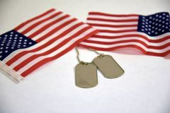Placas de identificación y banderas americanas en el fondo blanco imagen de archivo