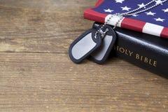 Placas de identificación con la biblia y la bandera americana Imágenes de archivo libres de regalías
