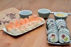 Placas de rolos de sushi do maki e de sushi do nigiri com alimento de japão dos salmões e do camarão na tabela com molho de soja Foto de Stock Royalty Free