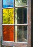 Placas de vidro coloridas em uma porta de madeira velha que abre sobre a um garde Imagem de Stock Royalty Free