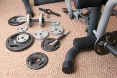 Placas del peso al lado de la máquina del ejercicio Imagenes de archivo
