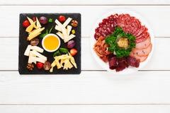 Placas del queso y de la carne en la tabla, endecha plana Imagen de archivo libre de regalías
