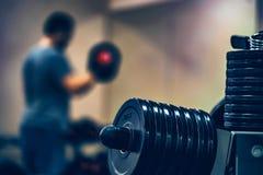 Placas do Barbell e do peso com homem trainning Imagem de Stock