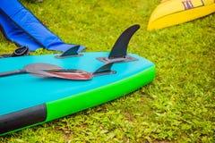 Placas do SUP que encontram-se na grama pelo rio, pelo lago ou pelo mar fotos de stock royalty free