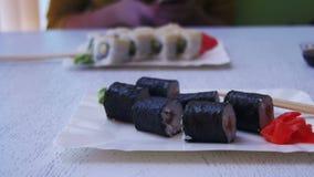 Placas do sushi Rolls com Nori em um restaurante japonês em uma tabela de madeira à moda branca Tiro da zorra video estoque