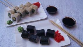 Placas do sushi Rolls em um restaurante japonês em uma tabela de madeira à moda branca Tiro da zorra video estoque