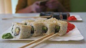 Placas do sushi Rolls em um restaurante japonês em uma tabela de madeira à moda branca Tiro da zorra vídeos de arquivo