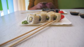 Placas do sushi Rolls em um restaurante japonês em uma tabela de madeira à moda branca Tiro da zorra filme