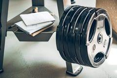 Placas e cadernos do peso do barbell da aptidão no gym Fotografia de Stock