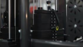 Placas pesadas do ferro no simulador dos esportes no gym da aptidão vídeos de arquivo