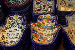 Placas pintadas da lembrança no contador na loja do Jerusalém, Israel Ornamento nacional em uma placa sob a forma de Hamsa imagem de stock