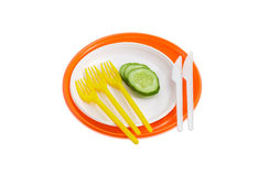 Placas plásticas descartáveis alaranjadas e brancas, pepino, forquilhas e Foto de Stock