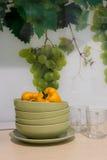 Placas, tazas, uvas, cocina Imagen de archivo