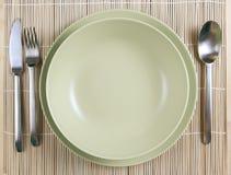 Placas verdes com faca e forquilha e colher Fotos de Stock