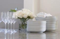 Placas, vidros & rosas no contador Foto de Stock