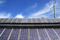 Placas y molino de viento solares bajo el cielo azul Imágenes de archivo libres de regalías
