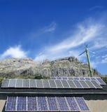 Placas y molino de viento solares bajo el cielo azul Fotos de archivo