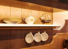 Placas y servicio de mesa blancos en un armario Imagen de archivo libre de regalías