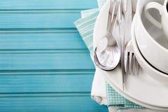 Placas y tazas blancas en el tablero de madera azul Imagenes de archivo