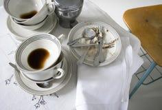 Placas y tazas de café sucias en una tabla Imagen de archivo