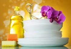 Placas y tazas, detergente del plato, esponjas, flor de la orquídea en amarillo foto de archivo