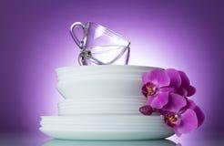 Placas y tazas limpias en el fondo púrpura brillante adornado con la rama de la orquídea imagen de archivo