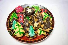 Placchi con i biscotti saporiti del pan di zenzero di Natale su Backgrou bianco Immagine Stock Libera da Diritti