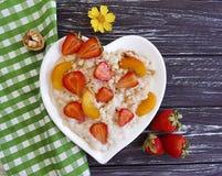 Placchi il porridge della farina d'avena del cuore, la fragola fresca dell'estate, albicocca su un fondo di legno fotografie stock