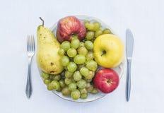 Placchi in pieno dei frutti naturali - l'uva, la mela, pera Fotografia Stock