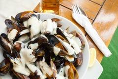 Placchi in pieno delle cozze con la salsa di aglio sulla tavola Immagine Stock Libera da Diritti