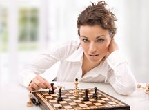 Place. Young businesswoman playing chess in modern place stock image