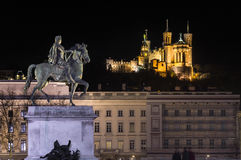 Place Bellecour Lyon France. Place Bellecour statue of King Louis XIV and The Basilica Notre Dame de fourviere on the background at night. Lyon France Stock Photo