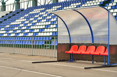 The place for a coach at the stadium. Sports Arena, the tribune with plastic seats, cabin with bright seating for players and managers team, next to the brown royalty free stock image
