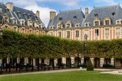 Place des Vosges: square in Le Marais, Paris, Fran. Garden and housefronts on Place des Vosges in Le Marais, Paris (France Stock Photo