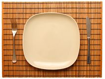 Place with empty dish. And flatware on a nice table mat Stock Photos