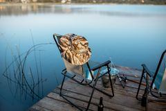 Place for fishing with tackles on the lake. Folding armchair with hat and tools for fishing on the wooden pier on the lake in the morning stock photo