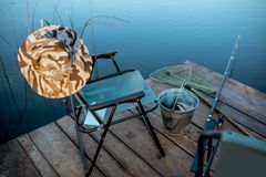 Place for fishing with tackles on the lake. Folding armchair with hat and tools for fishing on the wooden pier on the lake in the morning stock image