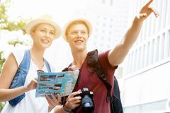 That is the place we are after. Happy young couple as tourists with a map Stock Images