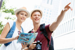 That is the place we are after. Happy young couple as tourists with a map Stock Photography