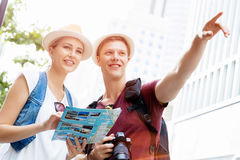 That is the place we are after. Happy young couple as tourists with a map Royalty Free Stock Photo