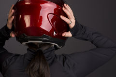 Woman Places Helmet on her Head Rear View Stock Photos